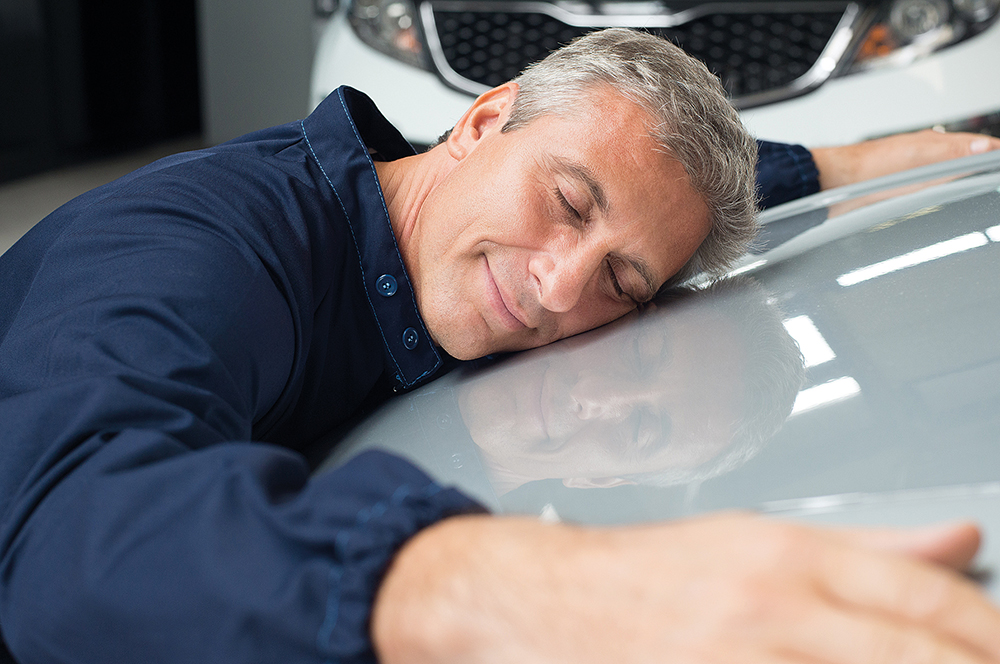 Closeup Of Mature Mechanic With Eyes Closed Lying On Car Bonnet Hugging