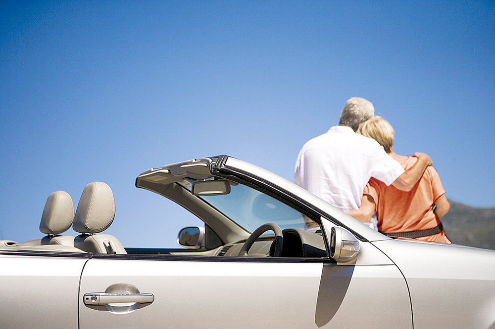Senior couple embracing, sitting on convertible silver car, rear view